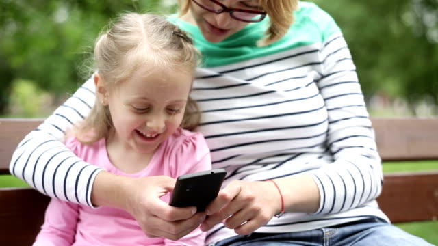 Mother and daughter looking at pictures on mobile phone