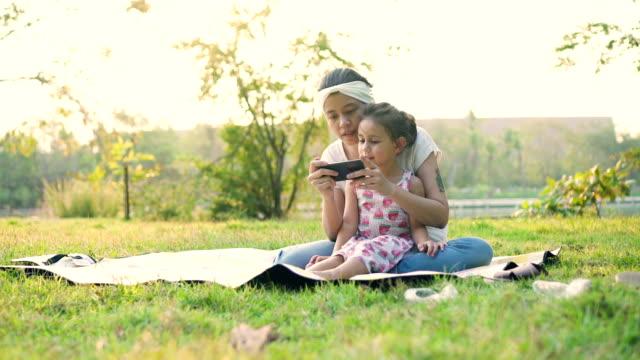 Moeder en dochter kijken naar foto's op mobiele telefoon