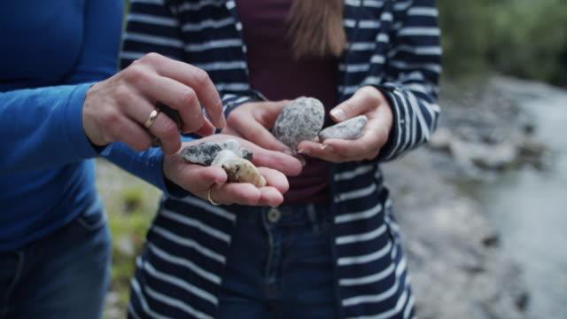 vidéos et rushes de mère et descendant regardant des pierres - pierre