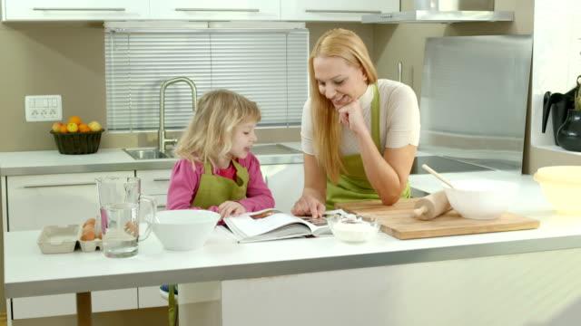 vídeos de stock, filmes e b-roll de hd dolly: mãe e filha olhando em um livro de receitas - receita