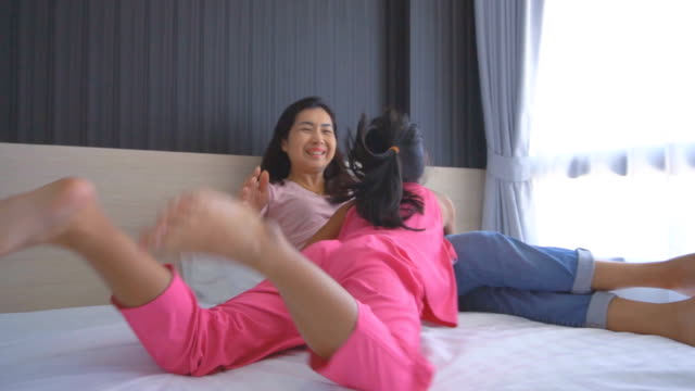 mother and daughter lying and playing on the bed at home - mixed race person stock videos & royalty-free footage