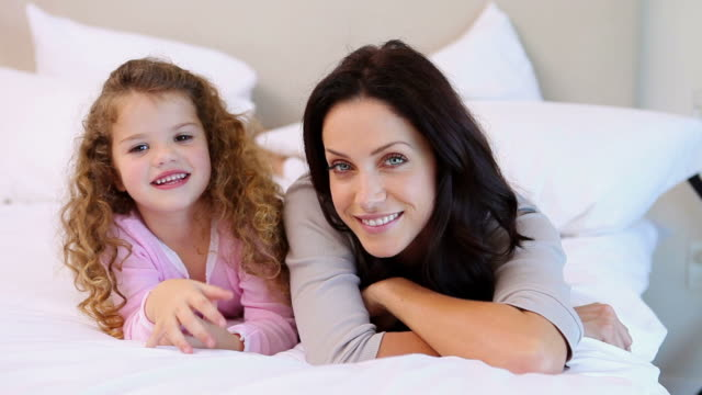 mother and daughter lying on the bed - braunes haar stock-videos und b-roll-filmmaterial