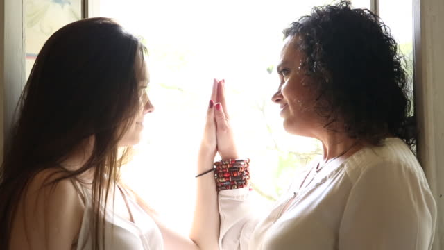 mother and daughter make contact with hands, indoor setting - ecuadorian ethnicity stock videos and b-roll footage
