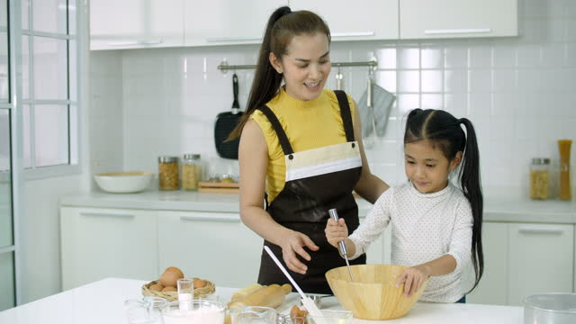 mother and daughter making a dough for cookies or a cake in kitchen - daughter stock videos & royalty-free footage