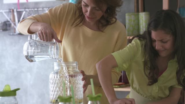 mother and daughter making a lemonade in teamwork - traditional lemonade stock videos & royalty-free footage