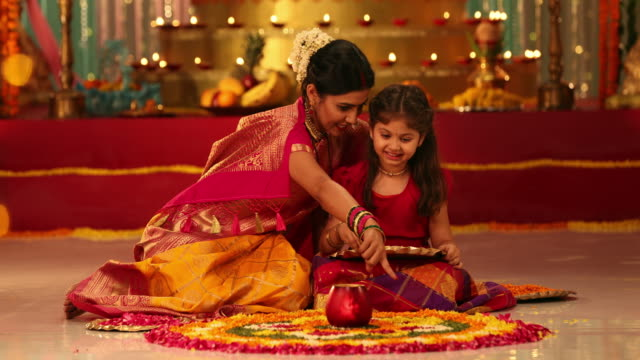 MS Mother and daughter making a rangoli with flower petals during Ganesh Chaturthi / New Delhi, Delhi, India