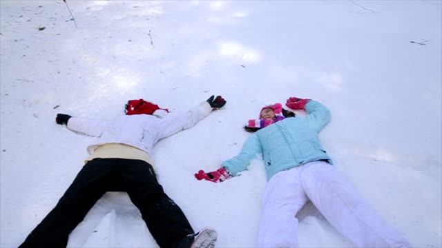 Mother and daughter  making a snow angel