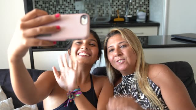 mother and daughter making a video chat on mobile - messaggistica online video stock e b–roll
