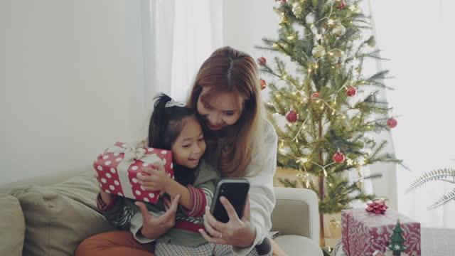 クリスマスの時間にビデオ会議を作る母と娘 - 贈り物点の映像素材/bロール