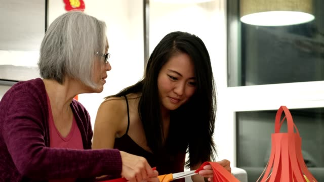 mother and daughter making chinese new year decorations - 65 69 years stock videos & royalty-free footage