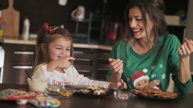 母親和女兒一起做聖誕餅乾在家庭廚房,他們有樂趣和裝飾甜餅乾。 - 裝飾 個影片檔及 b 捲影像