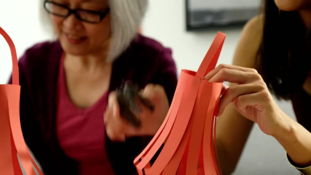 mother and daughter making decorations for chinese new year celebrations - 65 69 years stock videos & royalty-free footage