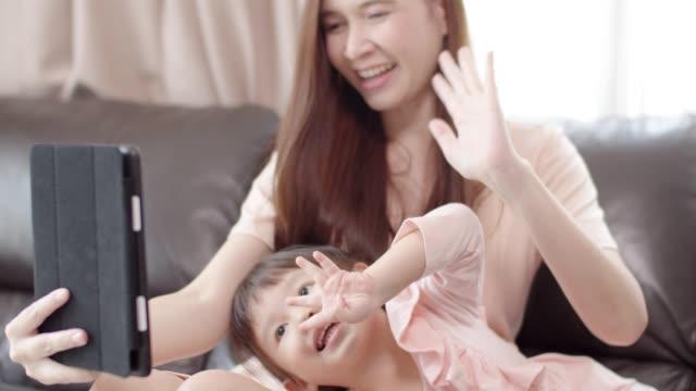 mutter und tochter machen entfernung videoanruf auf digitalen tablet. - little girl webcam stock-videos und b-roll-filmmaterial