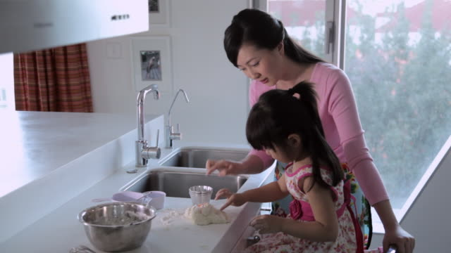 MS TU Mother and daughter making food together in kitchen / China