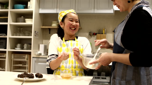 mother and daughter making miso dumpling in cooking class - domestic kitchen stock-videos und b-roll-filmmaterial