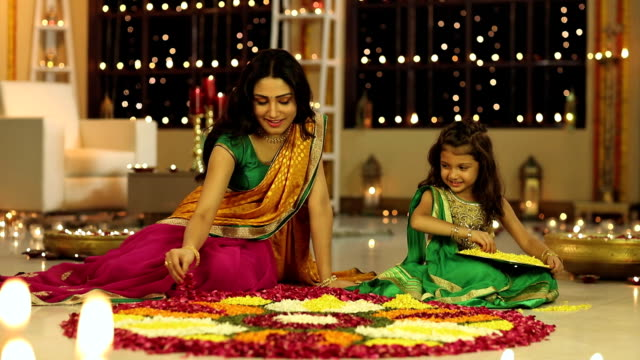 MS PAN Mother and daughter making rangoli with flower during Diwali festival