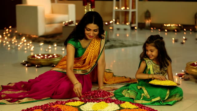 MS Mother and daughter making rangoli with flower during Diwali festival
