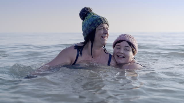 mother and daughter messing about in a cold sea in winter - cold temperature stock videos & royalty-free footage