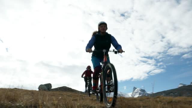 Mother and daughter mountain biking down alpine trail below Matterhorn