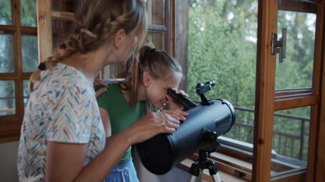 stockvideo's en b-roll-footage met moeder en dochter die aard waarnemen gebruikend telescoop - astronomietelescoop