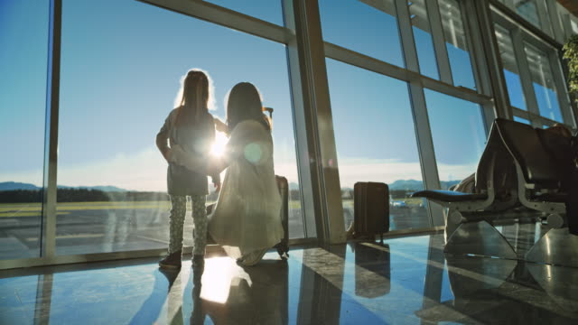 mother and daughter observing the sun shining on the runway at the airport - airport stock videos and b-roll footage
