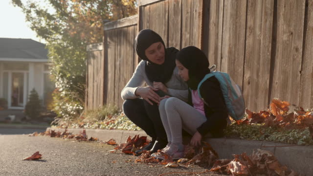 4k uhd: mother and daughter of middle eastern descent sit on a curb - equality stock videos & royalty-free footage