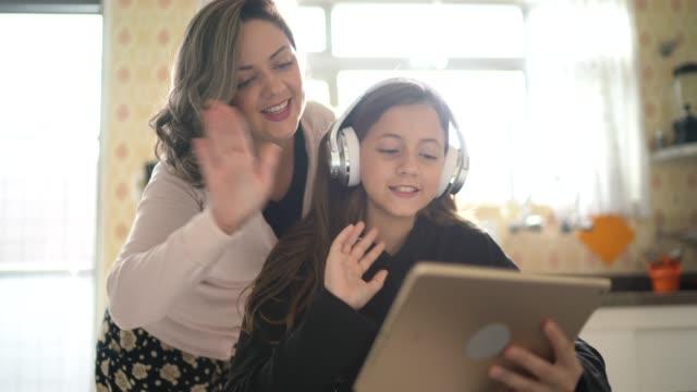 vídeos y material grabado en eventos de stock de madre e hija en una videollamada usando tableta digital en casa - cuarentena