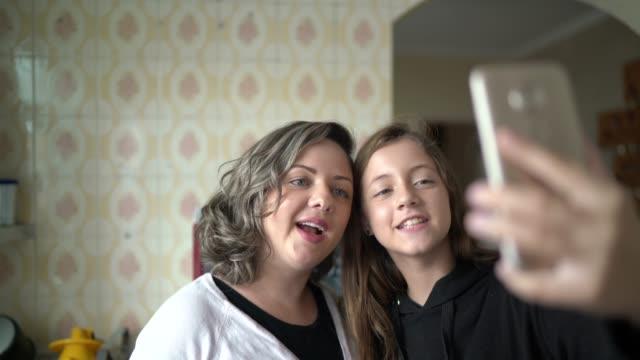 vídeos de stock, filmes e b-roll de mãe e filha em um vídeo chamando usando celular em casa - sentir a falta emoção