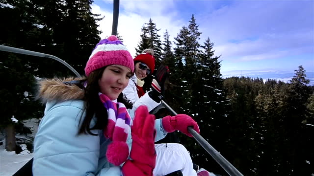 Mother and daughter on ski lift at winter vacation