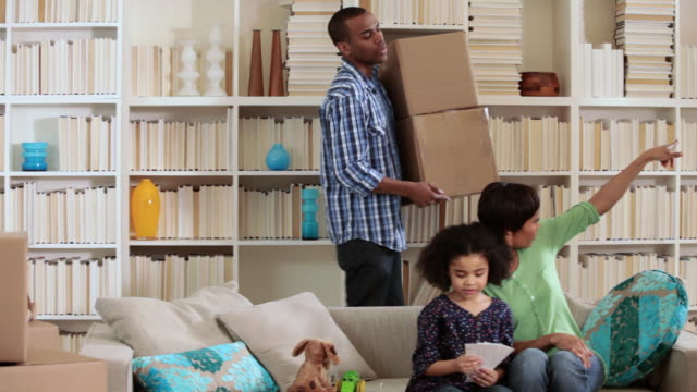 vídeos de stock, filmes e b-roll de mother and daughter on sofa, father walks past with cardboard box - moving past