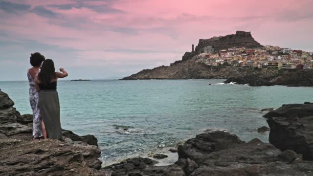 mother and daughter on the rocks in castelsardo, sardinia - sassari stock videos & royalty-free footage