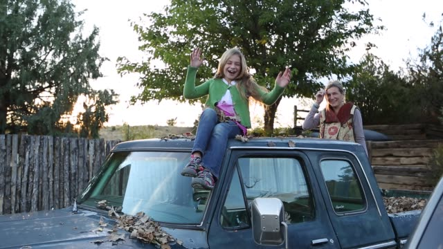 mother and daughter on top of old pick up truck