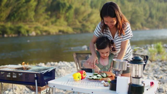 vidéos et rushes de mère et fille à l'extérieur par la rivière coupant des légumes - famille avec un enfant