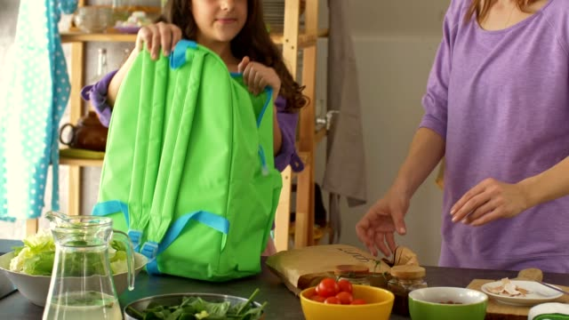 mother and daughter packing school lunch in a backpack - backpack stock videos & royalty-free footage