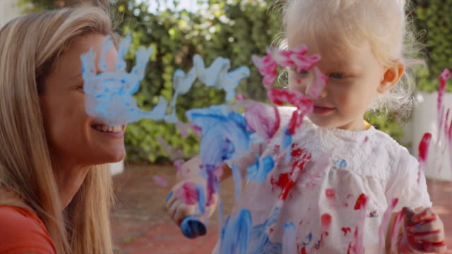 mother and daughter painting on window - stained stock videos & royalty-free footage