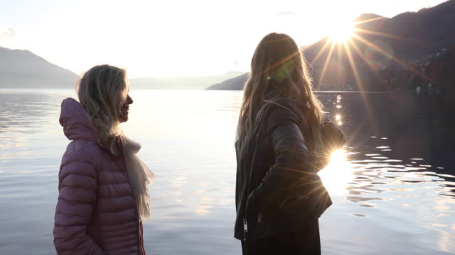 mother and daughter pause on lake edge at sunrise - blonde hair stock videos & royalty-free footage