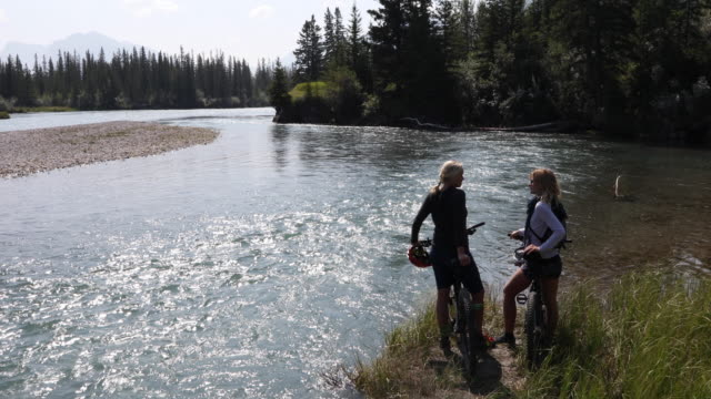 Mother and daughter pause with bikes by mountain river