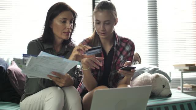 vídeos de stock, filmes e b-roll de contas pagando da matriz e da filha em linha no telefone esperto - batendo com a cabeça na parede
