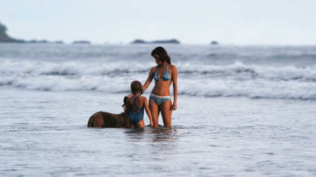 mother and daughter petting a dog in the ocean