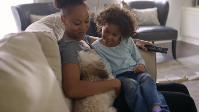 Mother and daughter petting dog on sofa