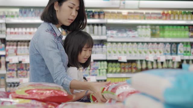vídeos y material grabado en eventos de stock de madre e hija recogida en un paquete en supermarket.4k - embalaje
