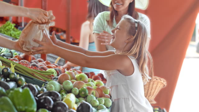 mother and daughter picking out produce at a market stall - fruit stock videos & royalty-free footage