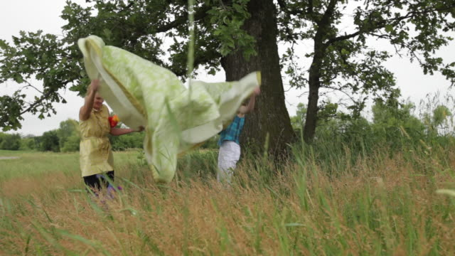 mother and daughter placing picnic blanket on grassy field - breit stock-videos und b-roll-filmmaterial