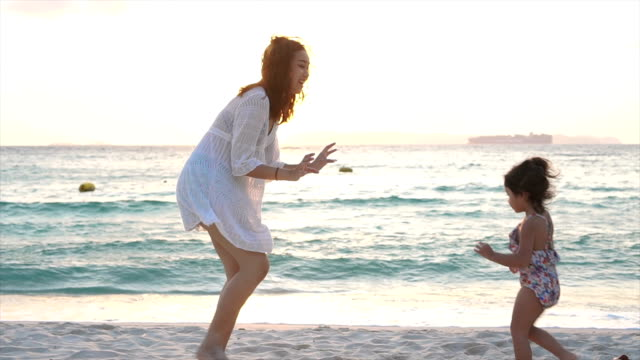 mother and daughter play and chase each other on the beach. - back lit stock videos & royalty-free footage