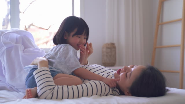 mother and daughter playing and touching cheek with a finger in the bedroom - korean ethnicity stock videos & royalty-free footage