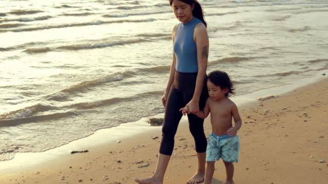 stockvideo's en b-roll-footage met moeder en dochter spelen op het strand - voetafdruk