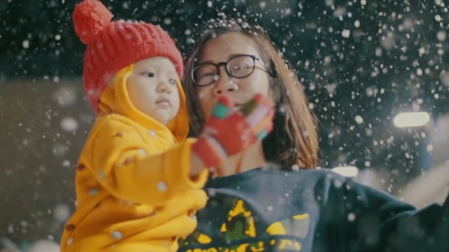 mother and daughter playing at winter festival, snowing - japanese mom stock videos & royalty-free footage