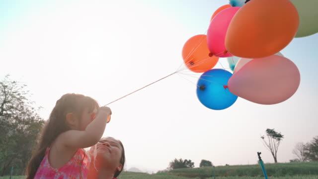 vídeos y material grabado en eventos de stock de madre e hija jugando globo - helio