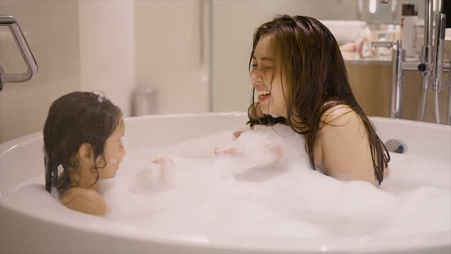 mother and daughter playing bubbles together in the bathtub - two generation family stock videos & royalty-free footage