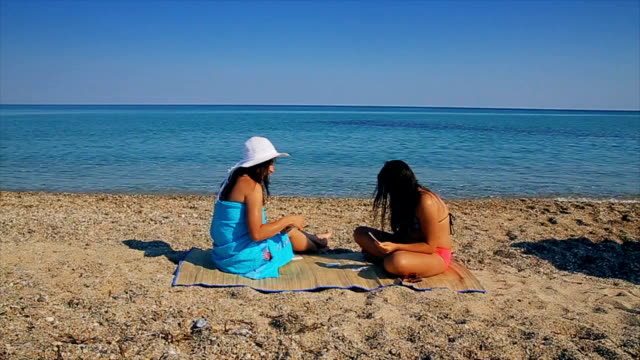 Mother and daughter playing cards on the beach on summer vacation